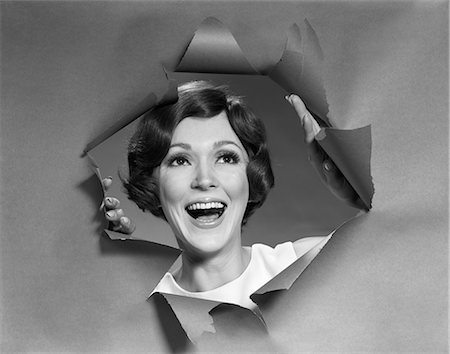 1970s PORTRAIT OF SMILING WOMAN LOOKING THROUGH A HOLE TORN IN PAPER Stock Photo - Rights-Managed, Code: 846-06111864