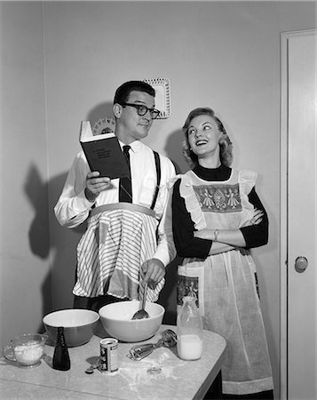 simsearch:846-02793283,k - 1950s COUPLE IN KITCHEN WITH HUSBAND LEARNING TO COOK WHILE WIFE WATCHES Stock Photo - Rights-Managed, Code: 846-06111877