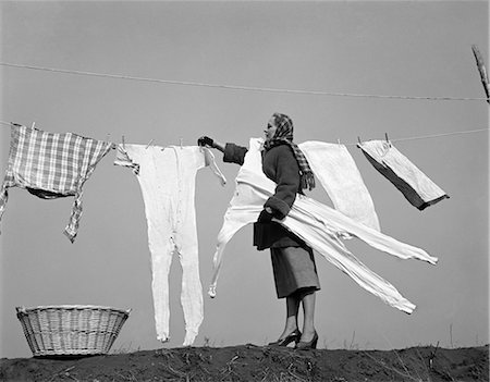 1950s HOUSEWIFE REMOVING FROZEN LONG JOHNS FROM CLOTHESLINE Stock Photo - Rights-Managed, Code: 846-06111878