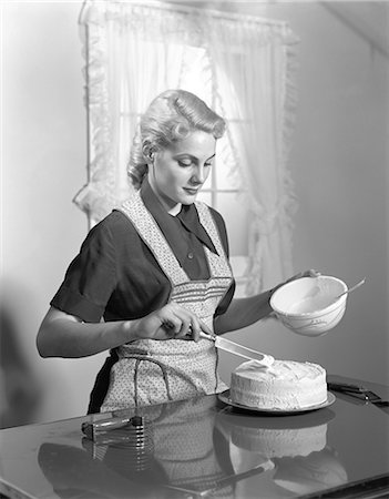 simsearch:846-02793283,k - 1940s WOMAN IN KITCHEN WEARING APRON FROSTING CAKE INDOOR Stock Photo - Rights-Managed, Code: 846-06111871