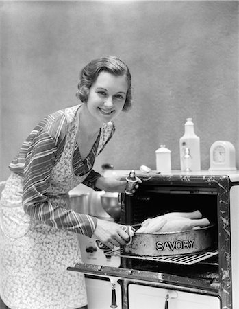simsearch:846-02793283,k - 1930s HOUSEWIFE IN APRON TAKING TURKEY IN PAN READING SAVORY OUT OF OVEN LOOKING AT CAMERA Stock Photo - Rights-Managed, Code: 846-06111884
