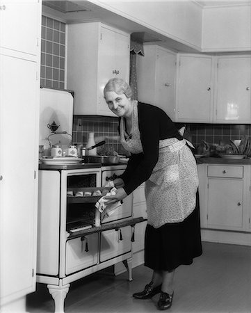 1940s ELDERLY WOMAN TAKING PAN OF ROLLS OUT OF OVEN LOOKING AT CAMERA Stock Photo - Rights-Managed, Code: 846-06111886