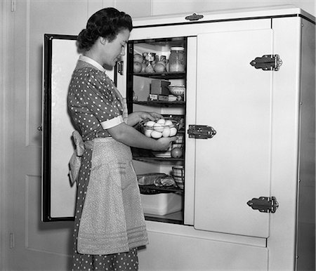 simsearch:846-02793283,k - 1930s HOUSEWIFE IN APRON TAKING EGGS OUT OF BOWL FROM ICEBOX Stock Photo - Rights-Managed, Code: 846-06111887