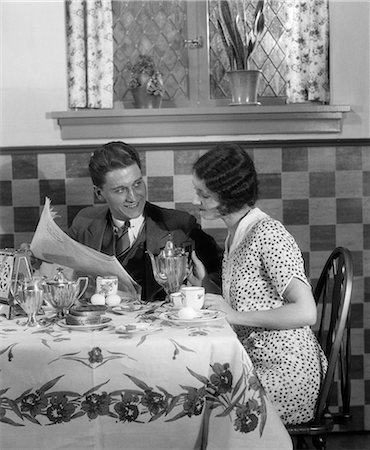 simsearch:846-02793283,k - 1920s 1930s COUPLE AT BREAKFAST TABLE LOOKING OVER NEWSPAPER WIFE GETTING READY TO POUR COFFEE FROM SILVER POT Stock Photo - Rights-Managed, Code: 846-06111889