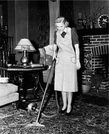 1930s 1940s WOMAN HOUSEWIFE WEARING APRON PUSHING ELECTRIC VACUUM CLEANER IN ORNATE LIVING ROOM HOUSE CHORE Stock Photo - Rights-Managed, Code: 846-06111883