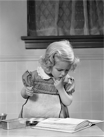 1940s LITTLE GIRL  PLAYING IN KITCHEN WEARING APRON LOOKING IN COOKBOOK GETTING READY TO BAKE Stock Photo - Rights-Managed, Code: 846-06111914