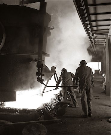 1960s PAIR OF STEEL WORKERS WEARING HARD HATS STIRRING & STOKING MOLTEN METAL POURING FROM CRUCIBLE Stock Photo - Rights-Managed, Code: 846-06111910