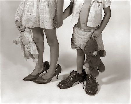 1950s 1960s CLOSE-UP OF LITTLE GIRL & BOY FROM NECK DOWN WEARING PARENTS' SHOES Stock Photo - Rights-Managed, Code: 846-06111921