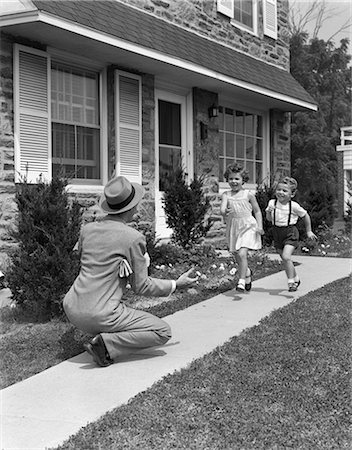 1950s MAN FATHER ARMS OUT KNEELING IN FRONT OF SUBURBAN HOME TO GREET HAPPY RUNNING WELCOME HOME SON AND DAUGHTER Stock Photo - Rights-Managed, Code: 846-06111955