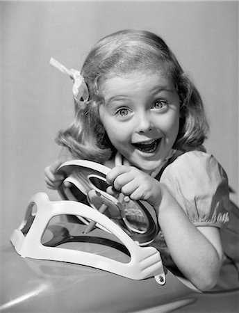 1950s PORTRAIT OF LITTLE GIRL DRIVING TOY CAR WITH EXCITED EXPRESSION LOOKING AT CAMERA Stock Photo - Rights-Managed, Code: 846-06111959