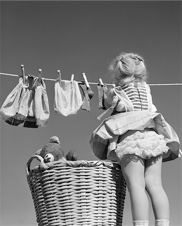 1950s BACK VIEW OF GIRL HANGING LAUNDRY WIND BLOWING SKIRT TO SHOW RUFFLED PANTIES Stock Photo - Rights-Managed, Code: 846-06111975