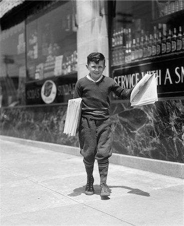 1930s NEWSBOY IN KNICKERS WALKING DOWN STREET HAWKING PAPERS Stock Photo - Rights-Managed, Code: 846-06111984