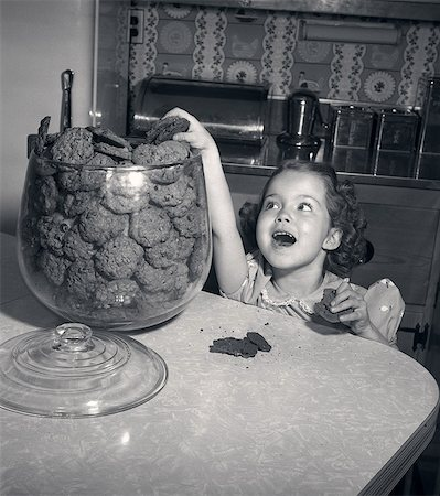1950s WIDE-EYED GIRL WITH MOUTH AGAPE REACHING UP INTO COOKIE JAR TAKING ANOTHER CHOCOLATE CHIP COOKIE Stock Photo - Rights-Managed, Code: 846-06111981