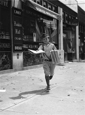 1930s NEWSPAPER BOY IN KNICKERS WALKING TOWARDS CAMERA ON STREET HOLDING PHILADELPHIA INQUIRER Stock Photo - Rights-Managed, Code: 846-06111995
