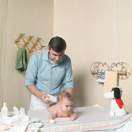 1970s FATHER CHANGING BABY GIRL DIAPER POWDERING BUTT Stock Photo - Rights-Managed, Code: 846-06112032