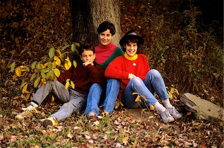 family shoes - 1980s FAMILY MOTHER SON AND DAUGHTER SITTING AT BASE OF TREE IN WOODS AUTUMN Stock Photo - Rights-Managed, Code: 846-06112075