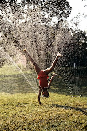 LITTLE GIRL CARTWHEELING THROUGH LAWN SPRINKLER Stock Photo - Rights-Managed, Code: 846-06112076