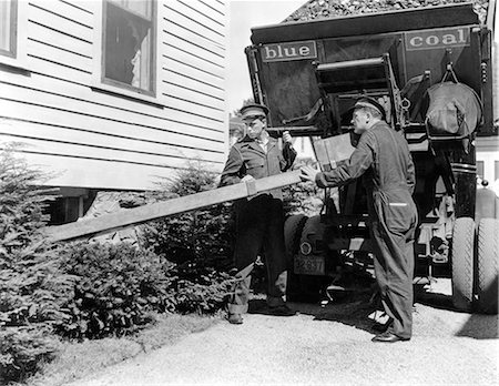 1930s 1940s COAL TRUCK WITH TWO SERVICE MEN MAKING HOME DELIVERY COAL CHUTE INTO BASEMENT Stock Photo - Rights-Managed, Code: 846-06112154