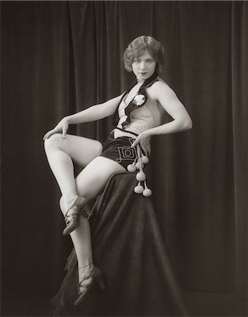 erotic female figures - 1920s SIDE VIEW OF FLAPPER WOMAN IN VELVET HOT PANTS & SEQUINED VEST SITTING ON PEDESTAL WITH LEGS CROSSED LOOKING TOWARD CAMERA Stock Photo - Rights-Managed, Code: 846-06112240