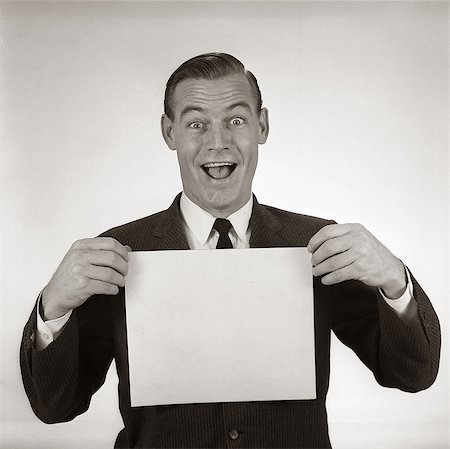 1950s 1960s EXCITED BUSINESSMAN LOOKING AT CAMERA HOLDING BLANK WHITE CARD Stock Photo - Rights-Managed, Code: 846-06112277