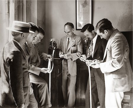 1930s BROKERS BUSINESSMEN READING TICKER TAPE AS IT COMES OUT OF GLASS DOMED MACHINE Stock Photo - Rights-Managed, Code: 846-06112288