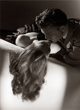 1940s 1950s ROMANTIC COUPLE EMBRACING ABOUT TO KISS ON SOFA Stock Photo - Rights-Managed, Code: 846-06112372