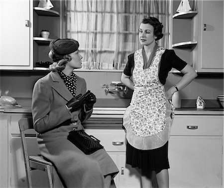 1930s 1940s TWO WOMEN SITTING IN KITCHEN TALKING ONE HOUSEWIFE HOMEMAKER IN APRON ONE IN COAT AND HAT VISITING TOGETHER GOSSIP Stock Photo - Rights-Managed, Code: 846-06112396