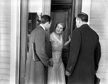 1930s 1940s TWO DOOR-TO-DOOR SALES SALESMEN TALKING TO HOUSEWIFE AT FRONT DOOR MAKING SALES PRESENTATION Stock Photo - Rights-Managed, Code: 846-06112404