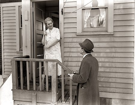 1940s 1930s MAN DOOR-TO-DOOR SALESMAN TALKING WOMAN TO HOUSEWIFE AT BACK DOOR Stock Photo - Rights-Managed, Code: 846-06112403