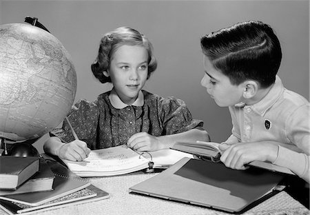 1960s BOY AND GIRL DOING HOMEWORK TOGETHER GLOBE AND BOOKS ON TABLE STUDIO INDOOR Stock Photo - Rights-Managed, Code: 846-06112421