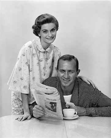simsearch:846-02793283,k - 1960s HUSBAND WIFE WEARING PAJAMAS AT BREAKFAST TABLE WOMAN BEHIND MAN HOLDING NEWSPAPER BOTH SMILING AND LOOKING AT CAMERA Stock Photo - Rights-Managed, Code: 846-06112495