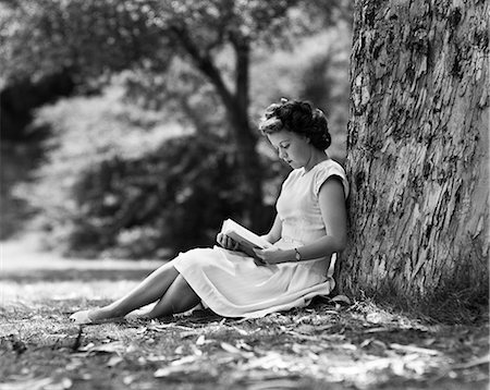 1950s YOUNG WOMAN READING BOOK SITTING UNDER TREE Stock Photo - Rights-Managed, Code: 846-07200045