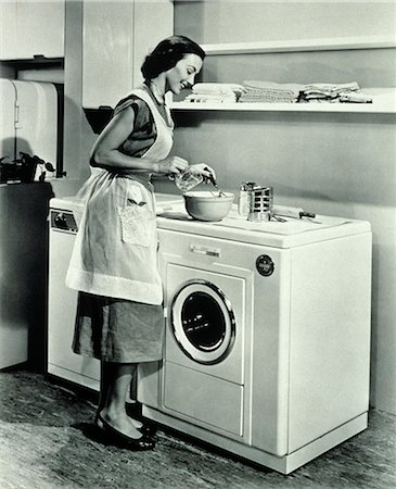 1950s  HOUSEWIFE USING TOP OF WASHING MACHINE AND DRYER AS KITCHEN COUNTER Stock Photo - Rights-Managed, Code: 846-07200056