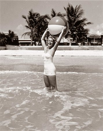 1950s SMILING WOMAN STANDING IN OCEAN SURF HOLDING PLASTIC BEACH BALL OVER HEAD LOOKING AT CAMERA Stock Photo - Rights-Managed, Code: 846-07200057