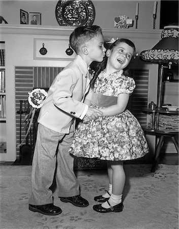 j1950s LITTLE BOY IN SUIT AND TIE TRYING TO KISS LITTLE GIRL IN PARTY DRESS Stock Photo - Rights-Managed, Code: 846-07200088