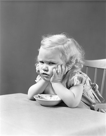 1940s UNHAPPY GRUMPY LITTLE BLONDE GIRL SITTING IN HIGHCHAIR REFUSING TO EAT Stock Photo - Rights-Managed, Code: 846-07200081