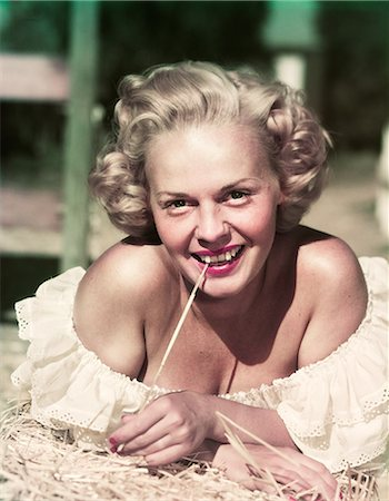 1940s 1950s PORTRAIT SMILING BLOND WOMAN WEARING OFF THE SHOULDER RUFFLED BLOUSE LYING ON BED OF HAY LOOKING AT CAMERA Stock Photo - Rights-Managed, Code: 846-07200124