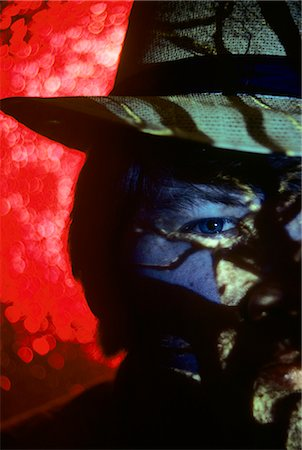 1980s CLOSE-UP DETAIL MAN'S HEAD FACE AND EYE WEARING HAT RED BACKGROUND CRIMINAL SPY CRIME MYSTERY Stock Photo - Rights-Managed, Code: 846-07760700