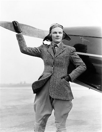 1930s WOMAN AVIATOR PILOT STANDING NEXT TO AIRPLANE ONE HAND ON PROPELLER FLIGHT GOGGLES CAP TWEED SUIT FASHION Stock Photo - Rights-Managed, Code: 846-07760703