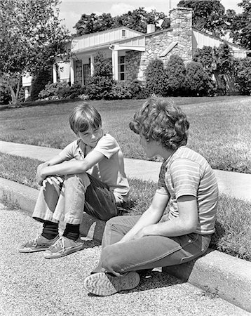 1970s TWO EARLY TEENAGE BOYS SITTING ON CURB SUBURBAN NEIGHBORHOOD TALKING Stock Photo - Rights-Managed, Code: 846-07760713