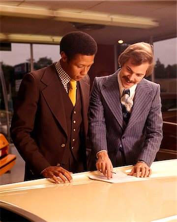 1970s TWO MEN CUSTOMER AND SALESMAN READING SALES CONTRACT ON HOOD OF NEW CAR IN DEALERSHIP SALES SHOWROOM Stock Photo - Rights-Managed, Code: 846-07760725