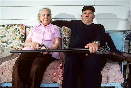 right - ELDERLY COUPLE WITH SHOTGUN & PISTOL SITTING ON PORCH GLIDER Stock Photo - Rights-Managed, Code: 846-07760735