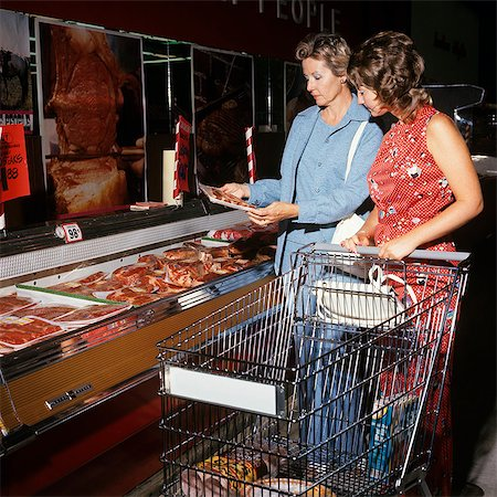 1970s TWO WOMEN MOTHER AND DAUGHTER PUSHING A SHOPPING CART IN MEAT DEPARTMENT OF SUPERMARKET Stock Photo - Rights-Managed, Code: 846-07760732
