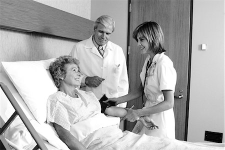 1980s ELDERLY WOMAN IN HOSPITAL BED HAVING BLOOD PRESSURE TAKEN BY FEMALE NURSE MALE DOCTOR STANDING BESIDE HER Stock Photo - Rights-Managed, Code: 846-07760749