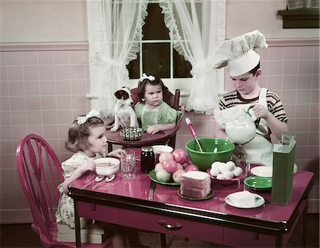 simsearch:846-02793283,k - 1940s 1950s BOY TWO GIRLS AT KITCHEN TABLE BOY IN TOQUE COOKING ONE GIRL EATING TODDLER AND PUPPY IN HIGH CHAIR Stock Photo - Rights-Managed, Code: 846-08030389