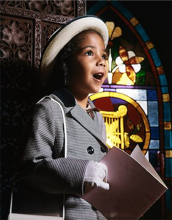 1960s AFRICAN AMERICAN GIRL IN CHURCH BY STAINED GLASS WINDOW HOLDING BOOKLET SINGING HYMN Stock Photo - Rights-Managed, Code: 846-08030399