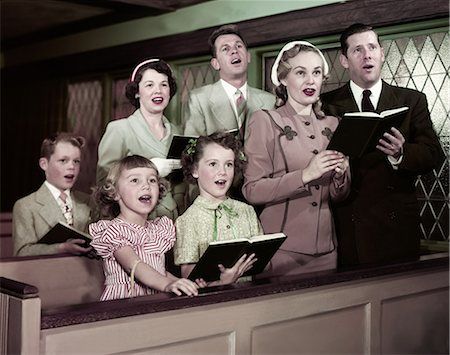 1950s TWO FAMILIES PARENTS CHILDREN IN CHURCH PEWS SINGING FROM HYMNAL BOOKS Stock Photo - Rights-Managed, Code: 846-08030415