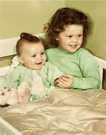 1940s 1950s SMILING LITTLE GIRL AND HAPPY BABY SISTER SITTING TOGETHER IN CORNER OF CRIB BED Stock Photo - Rights-Managed, Code: 846-08030418