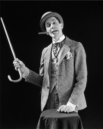 1910s 1920s CHARACTER CON MAN BARKER BOWLER HAT LOUD VAUDEVILLE TYPE CLOTHES POINTING CANE SMOKING CIGAR CONFIDENCE GAME Stock Photo - Rights-Managed, Code: 846-08030426