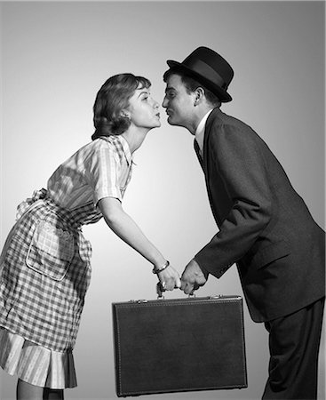 simsearch:846-02793283,k - 1950s 1960s HOMEMAKER WIFE IN CHECKED APRON KISSING BUSINESSMAN HUSBAND IN SUIT HAT AND TIE AS SHE HANDS HIM A BRIEFCASE Stock Photo - Rights-Managed, Code: 846-08030421
